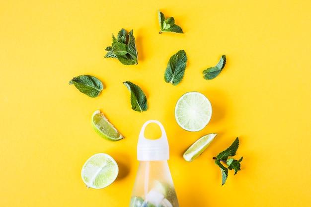 Ingrédients pour citron vert mojito et menthe sur fond jaune à côté d'une bouteille transparente