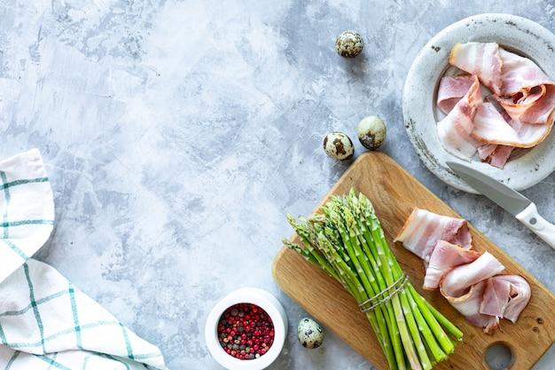 Ingrédients pour cuisiner sur un fond de béton gris. un tas d'asperges vertes fraîches, des œufs et du bacon. vue de dessus. espace copie