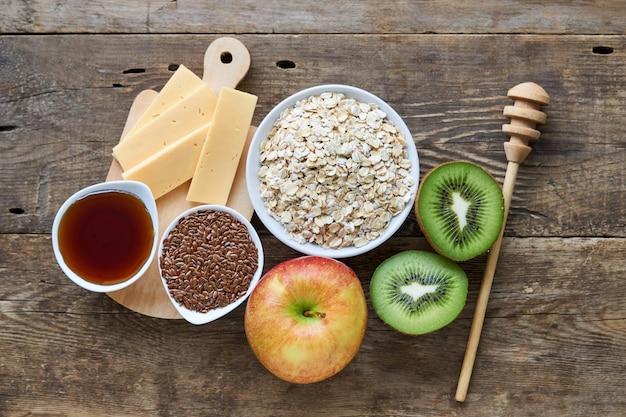 Ingrédients pour la cuisson de la bouillie d'avoine avec des fruits sur un fond en bois