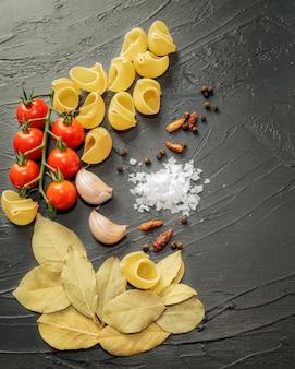 Ingrédients pour la cuisson de coquilles de pâtes aux épices et tomates cerises sur fond noir.