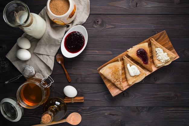 Ingrédients pour la cuisson des crêpes sur un fond en bois