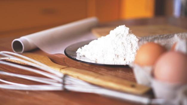 Ingrédients pour la cuisson du pain fait maison. oeufs, farine. fond en bois, vue latérale. flou et lumière