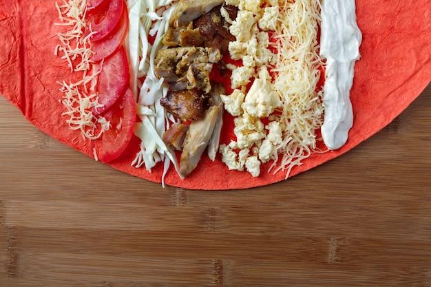 Les ingrédients pour la cuisson du shawarma reposent sur un pain pita. plat du moyen-orient à griller.
