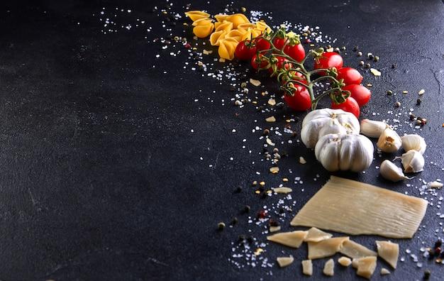Ingrédients pour la cuisson des pâtes sur fond noir.