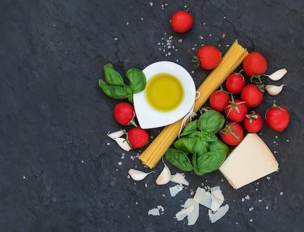 Ingrédients pour la cuisson des pâtes. spaghetti, huile d'olive, ail, parmesan, tomates et basilic frais sur un mur d'ardoise noire, vue de dessus, espace copie.