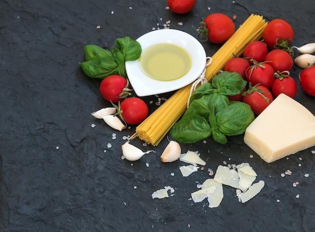 Ingrédients pour la cuisson des pâtes. spaghetti, huile d'olive, ail, parmesan, tomates et basilic frais
