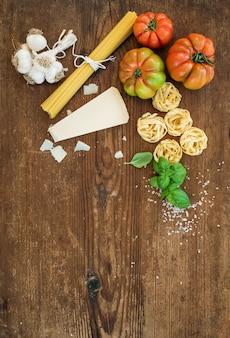 Ingrédients pour la cuisson des pâtes. spaghetti, tagliatelles, ail, parmesan, tomates et basilic frais sur bois rustique, vue de dessus, fond.