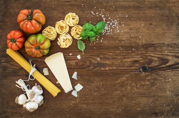 Ingrédients pour la cuisson des pâtes. spaghetti, tagliatelles, ail, parmesan, tomates et basilic frais sur fond en bois rustique, vue de dessus, espace copie.