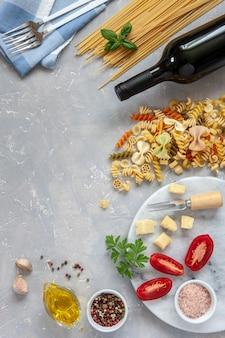 Ingrédients pour la cuisson des pâtes traditionnelles - fromage, tomates, condiments.