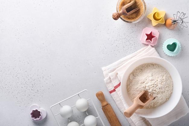Ingrédients pour la cuisson de pâtisseries maison. fond de cuisson avec de la farine, des œufs, des ustensiles de cuisine, des ustensiles et des moules à biscuits sur une table en marbre blanc. vue de dessus. style plat. maquette.