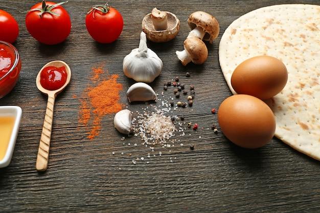 Ingrédients pour la cuisson des pizzas sur table en bois, gros plan