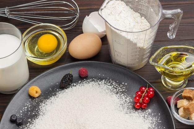 Ingrédients pour la cuisson de la tarte aux baies. baies, farine en assiette noire. tasse à mesurer avec farine, verre de lait, œuf cassé. surface en bois sombre. vue de dessus