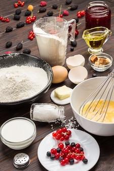 Ingrédients pour la cuisson de la tarte aux baies. baies, farine en assiette noire.