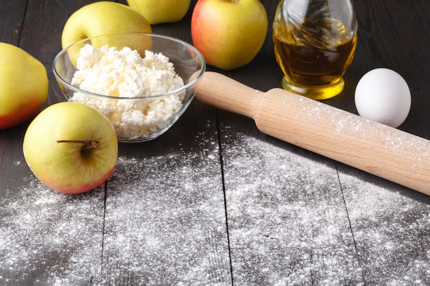 Ingrédients pour la cuisson de la tarte aux pommes. pomme fraîche, beurre, farine, sucre, épices sur un bois rustique.