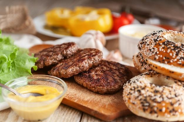 Ingrédients pour un délicieux burger maison. rouleau, bagel, avec une escalope juteuse de boeuf, sauces fromage feuilles de laitue fraîche