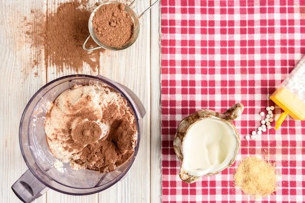 Ingrédients pour dessert soufflé au fromage cottage maison avec du cacao sur une table en bois blanc.