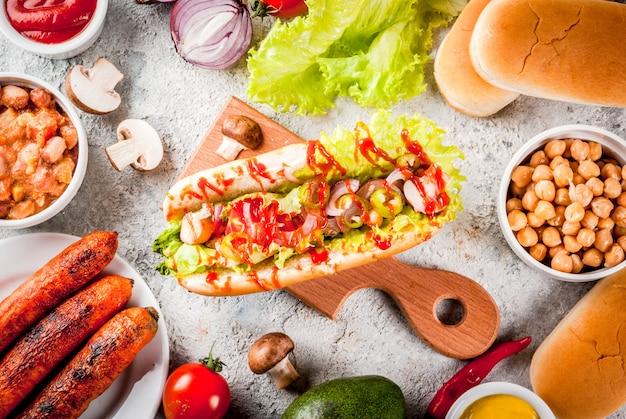 Ingrédients pour différents hot-dogs de carottes végétaliens faits maison, avec oignon frit, avocat, piment, champignons, tomates et haricots, fond en pierre grise vue de dessus