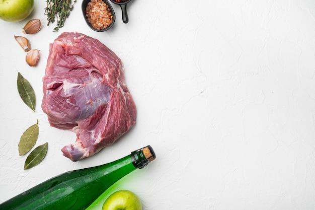 Ingrédients pour ensemble de longe de porc rôti, avec cidre sec de pomme, sur fond de table en pierre blanche, vue de dessus à plat, avec espace de copie pour le texte
