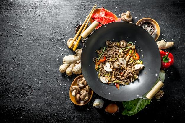 Ingrédients pour faire de délicieuses nouilles soba wok. sur table rustique noire