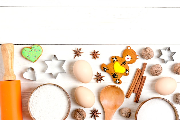 Ingrédients pour faire du pain d'épices - farine, sucre, œuf, cannelle, clou de girofle, noix, ustensiles de cuisson, ro