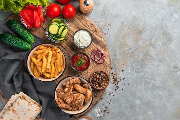 Ingrédients pour faire du shawarma, des tacos sur un mur gris avec un espace pour copier. vue de dessus, copiez l'espace.