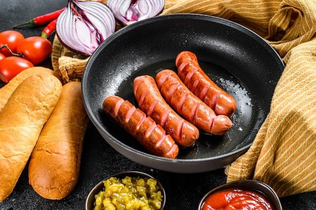 Ingrédients pour faire des hot-dogs maison. saucisses en casserole, petits pains frais, moutarde, ketchup, concombres. fond noir. vue de dessus