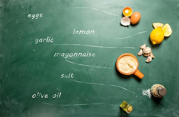 Ingrédients pour faire de la mayonnaise avec des inscriptions sur un tableau noir