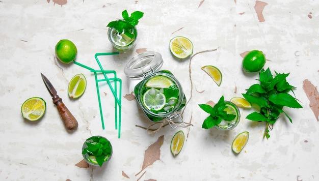 Ingrédients pour faire des mojitos - citron vert, feuilles de menthe, rhum, couteau à agrumes et une vieille table. vue de dessus