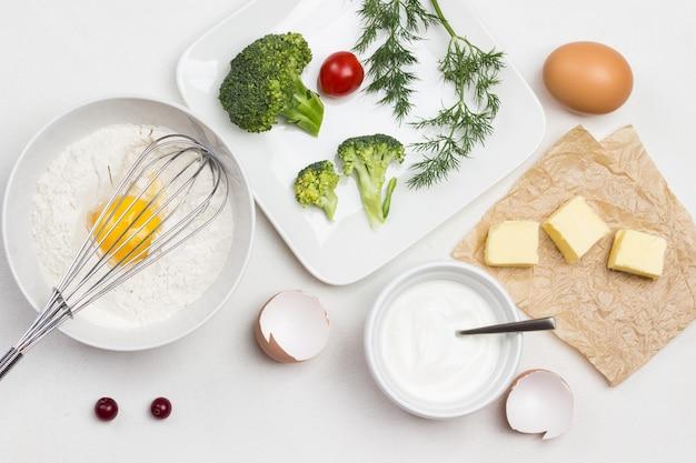 Ingrédients pour faire de la pâte. oeuf cassé avec de la farine dans un bol. fouetter sur un bol. beurre sur papier. brocoli, tomates et aneth en assiette. fond blanc. mise à plat