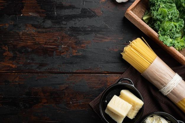 Ingrédients pour faire des pâtes. ensemble de spaghettis crus, sur la vieille table en bois sombre, vue de dessus à plat