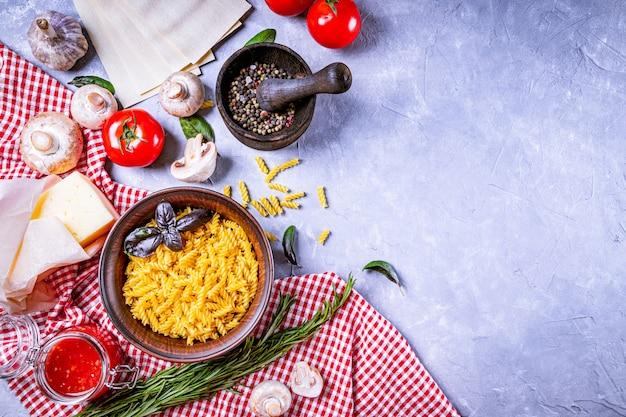 Ingrédients pour faire des pâtes italiennes sur fond gris, copie vue de dessus de l'espace.