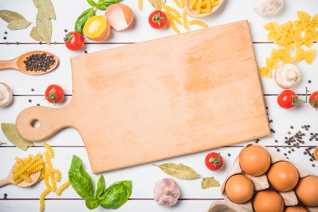 Ingrédients pour faire des pâtes avec une planche à découper au centre