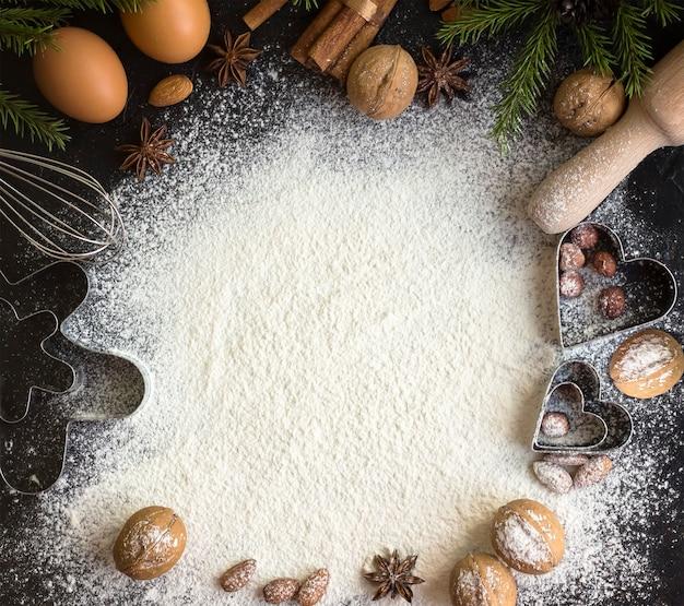 Ingrédients pour faire des pâtisseries de noël sur une pierre sombre.