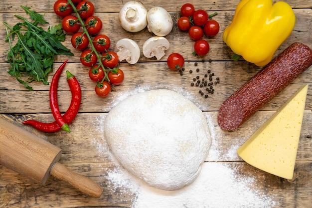 Ingrédients pour faire une pizza, avant la cuisson, sur une table en bois, vue de dessus, recette étape par étape