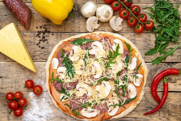 Ingrédients pour faire des pizzas et des pizzas crues avant la cuisson, sur une table en bois, vue de dessus, recette étape par étape