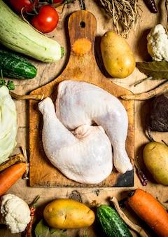 Ingrédients pour faire de la soupe au poulet sur une table en bois.