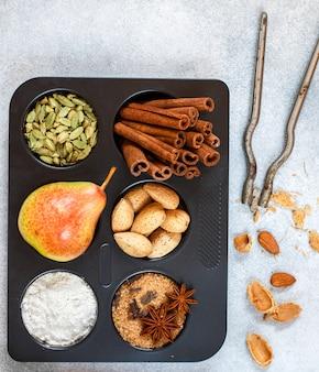 Ingrédients pour farine à cuire, poire aux fruits, cassonade, anis étoilé, cannelle, cardamome, clou de girofle, amandes