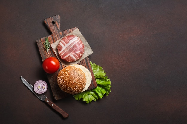 Ingrédients pour hamburger côtelette crue, tomates, laitue, brioche, fromage, concombre et oignon