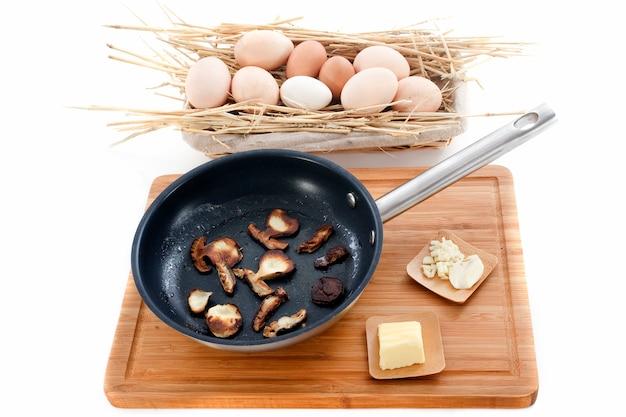 Ingrédients pour omelette aux champignons sur une planche à découper
