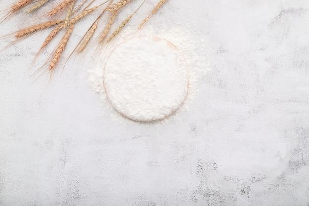 Les ingrédients pour la pâte à pizza maison avec des épis de blé, de la farine de blé et des grains de blé mis en place sur fond de béton blanc.