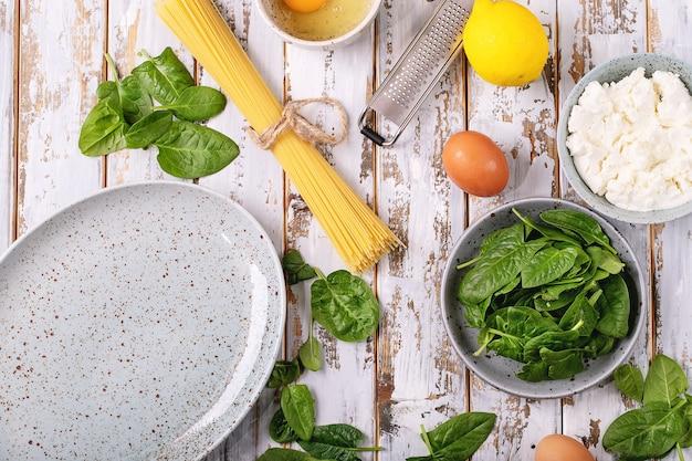 Ingrédients pour pâtes aux oeufs végétariens tagliatelles maison carbonara servi avec du fromage ricotta, des œufs et des épinards sur fond de bois blanc.