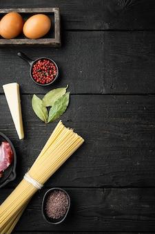 Ingrédients pour pâtes carbonara. ensemble de cuisine italienne traditionnelle, sur table en bois noir, vue de dessus à plat, avec copie espace