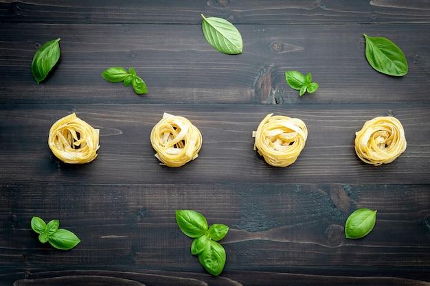 Ingrédients pour les pâtes faites maison sur un fond en bois foncé.