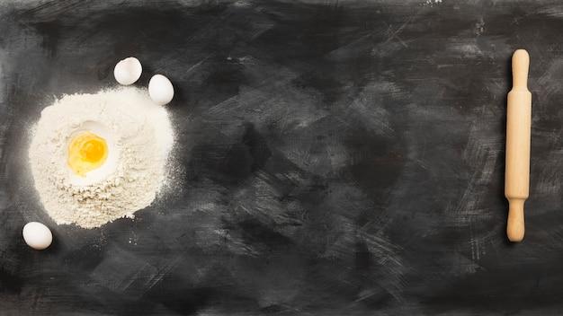 Ingrédients pour pâtisseries (farine, œufs) et rouleau à pâtisserie fond sombre. vue de dessus, espace copie. contexte alimentaire