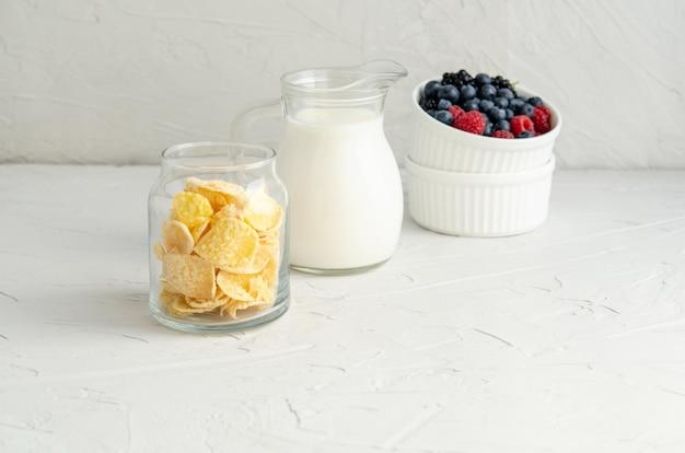Ingrédients pour un petit déjeuner sain - cornflakes, baies, lait