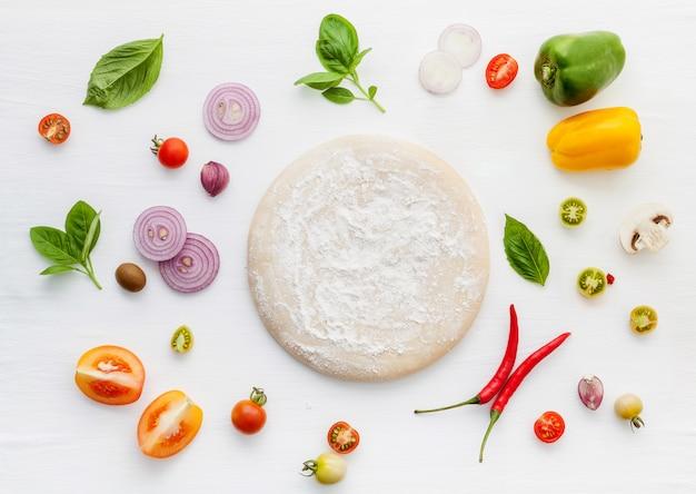 Les ingrédients pour une pizza maison sur un fond en bois blanc.