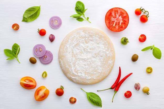 Les ingrédients pour une pizza maison sur fond de bois blanc.