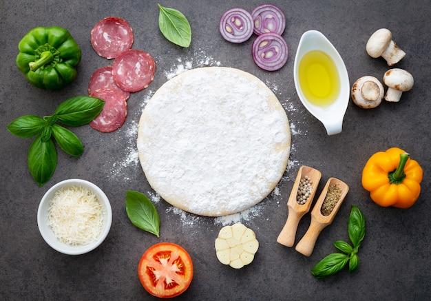 Les ingrédients pour une pizza maison sur fond de pierre sombre.