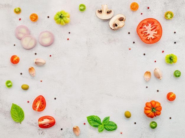 Les ingrédients pour la pizza maison mis en place sur fond de béton blanc.
