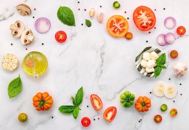 Les ingrédients pour la pizza maison mis en place sur fond de marbre blanc.